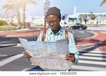 Outdoor Shot Of Handsome Fashionable Afro American Male Traveler With Backpack Standing In The Middl