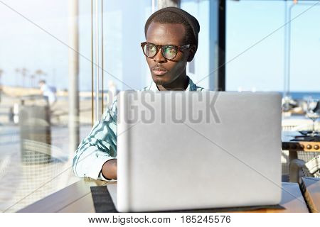 Serious Young African Americans Programmer Working On Notebook Pc At Coworking Space, Sitting In Fro