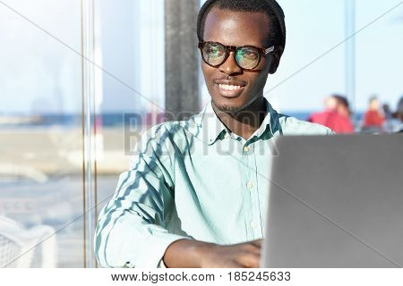 Cheerful Young Black Freelancer In Trendy Hat And Eyewear Smiling Happily, Having Inspired And Dream