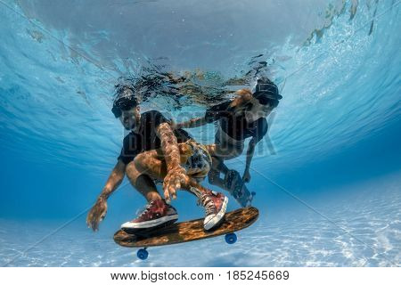 Man and Woman skateboarding underwater in the swimming pool