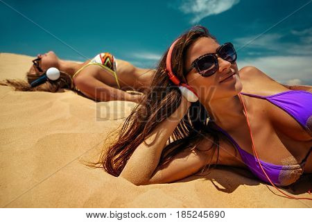 Young beautiful women relaxing and listening to music using headphones they are lying on sand