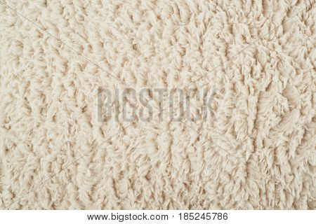 Close-up fragment of a beige colored artificial fur texture as a backdrop composition