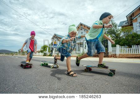 Little boys on longboard skates on the road