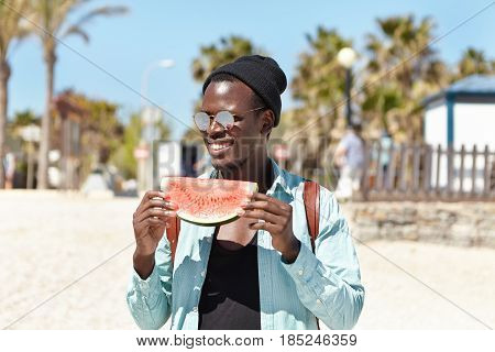 Outdoor Summer Portrait Of Attractive Trendy Looking Young Black Student With Knapsack Holding Slice