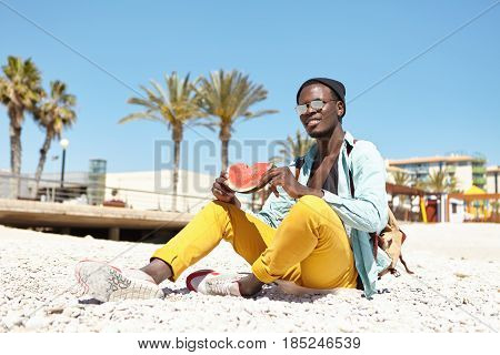 Outdoor Portrait Of Handsome Young African American Man With Knapsack Sitting On Pebble Beach Wearin