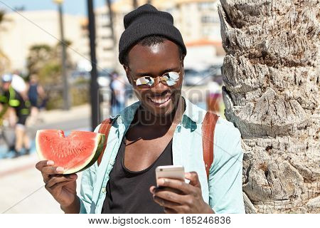 Cheerful Young Dark-skinned Male Spending Nice Time Outdoors, Enjoying Juicy Red-ripe Watermelon And