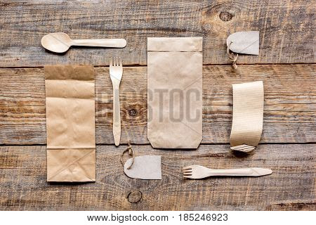 food delivery workdesk with paper bags and flatware on restourant wooden table background top view mock-up