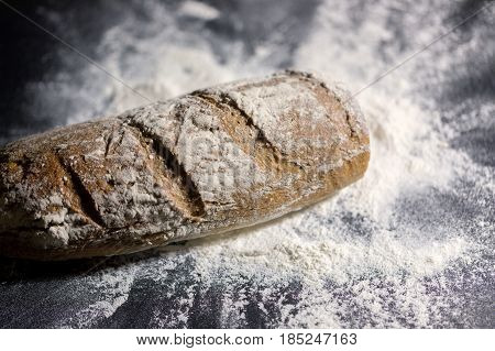 Fully baked bread on flour at the table