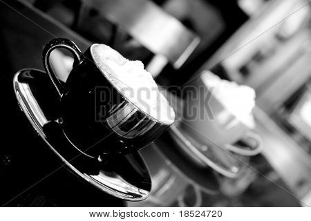 two coffee cups with whipped cream, black and white