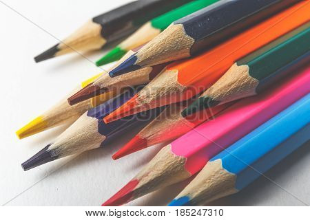 Toned background of colored pencils on white paper for art creativity closeup macro photo