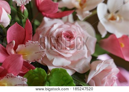 Close up Roses and other flowers from pastry mastic or sugar, decoration on a sweet cake