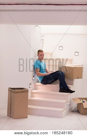 Happy young man sitting in stairway at home, using laptop computer with boxes around him