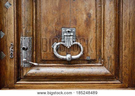 Old wooden door with metal handle knocker in Paris France. Antique wooden door of apartment building outdoor. Horizontal image