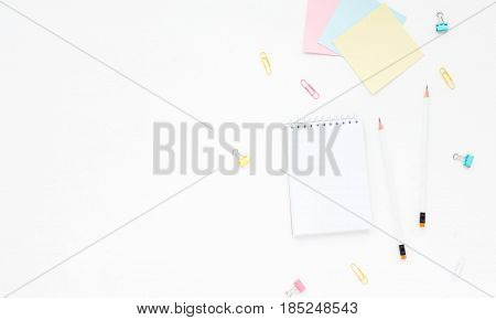 Colorful Woman's Workspace With Pink, Yellow And Turquoise Clips, Notebook And Pencil On White Backg