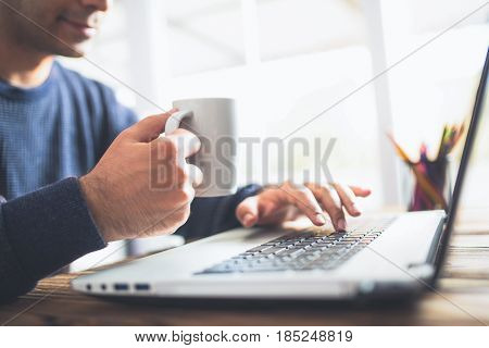 Man Typing On Computer Keyboard And Drinking Coffee