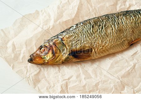 smoked herring fish on parchment paper wooden background