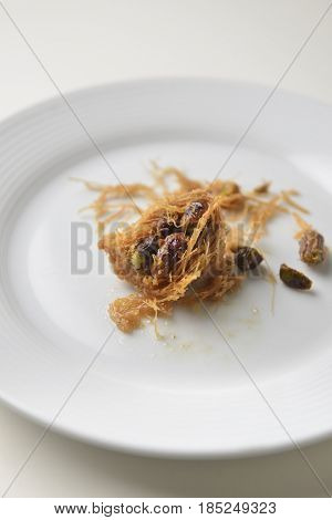 A leftover Baklava. A small piece of an arabic sweet left on a white plate.