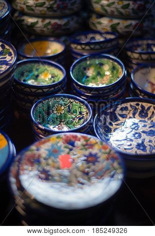Handcrafted turkish crockery and bowls with intricate decorative design, displayed in a souvenir shop. Close up of many traditional hand painted bowls.