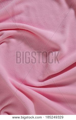 Soft and fluffy towel with small folds in baby pink color. Bath towel texture and background.