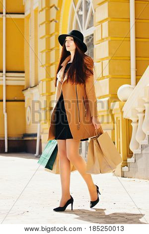 Walking With Purchases. Beautiful And Young Attractive Girl In Hat And Beige Coat Walking In The Cit