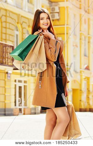 Shopping Beauty. Portrait Of Beautiful And Young Longhaired Girl Posing With Shopping Bags While Wal