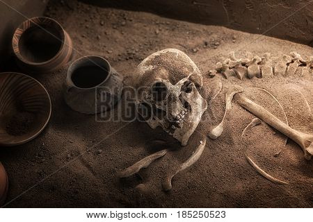 Ancient skeleton lying in grave with old pots