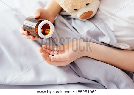 Sick Child Boy Takes Medication In Bed