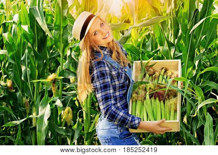 Happy Farmer. Portrait Of Beautiful And Young Smiling Redhaired Girl In Hat And Coveralls Holding A
