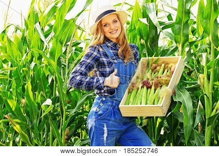 Big Harvest. Portrait Of Young And Attractive Smiling Girl In Hat And Coveralls Showing Big Thumb Up