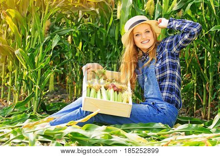 Harvest Time. Portrait Of Young And Attractive Smiling Girl In Hat And Coveralls Holding Box With Co