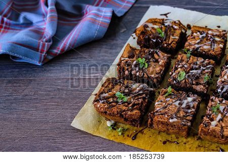 Delicious homemade brownie with dark and white chocolate sauce on the baking sheet.