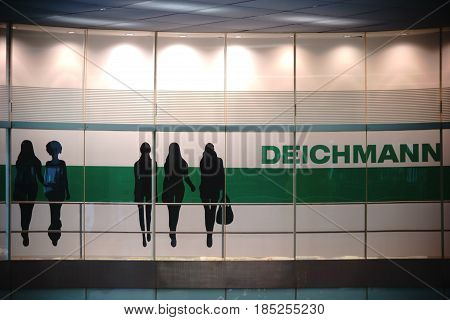 BERLIN, GERMANY - MAY 01: The illuminated logo with model silhouettes of shoes wholesale seller Deichman in Berlin's East Railway station on May 01, 2017 in Berlin.