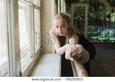 Young beautiful ballerina warming up in ballet class. Close up girl in black leotard stretch at ballet class stretching muscles at the barre