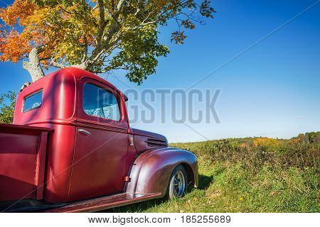 Old red farm truck parked under autumn tree. Blue sky background with copy space.