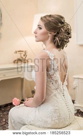 Beautiful bride brunette in white wedding dress with hairstyle and bright makeup