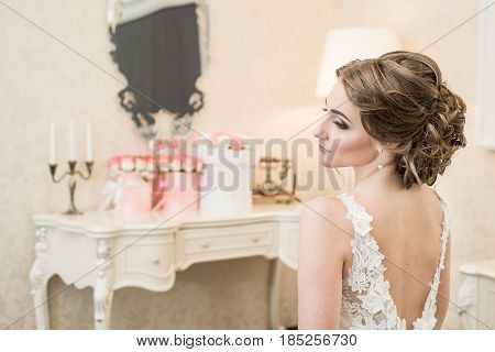 Beautiful bride brunette in white wedding dress with hairstyle and bright makeup for wedding