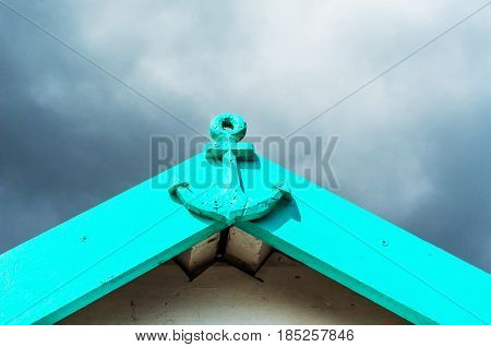 Metal decoration in the shape of anchor on the facade painted anchor nice decor green roof cloudy day