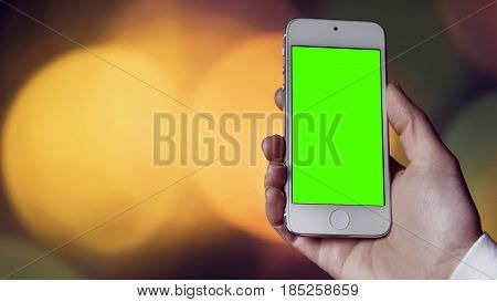 Woman's hand holds white smartphone before bokeh light coloured background