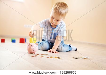 two years old child sitting on the floor and putting a euro money into a piggybank.