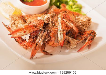 Crab claws in pepper sauce on a white plate