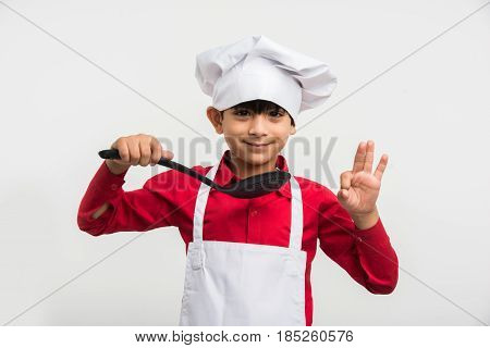 indian kid chef career, indian cute boy in chef or cook uniform over white background