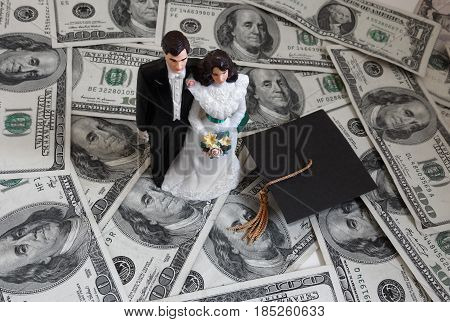 Plastic cake topper newlywed couple on cash with graduation cap -- student loan debt concept
