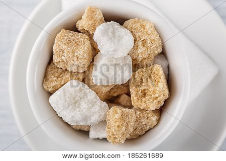 White sugar and brown sugar cane cube in white bowl on white background. Close up image.