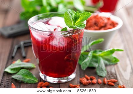 Healthy detox drink with goji berries infused in water with ice cold refreshing beverage