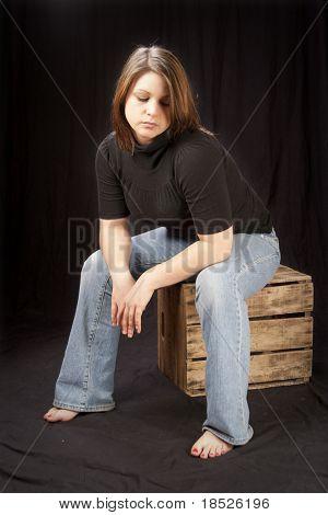 depressed teenaged girl seated on box