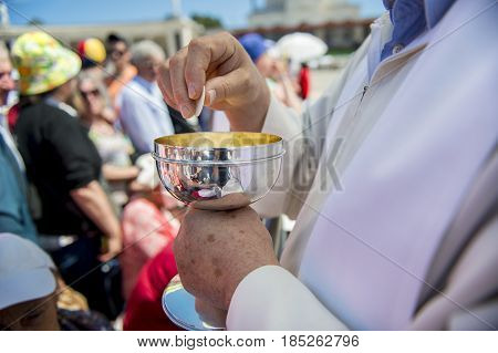 Fatima Portugal - May 13 2014: Priest holding a ciborium with sacramental bread at the Sanctuary of Fatima during the celebrations of the apparition of the Virgin Mary in Fatima Portugal.