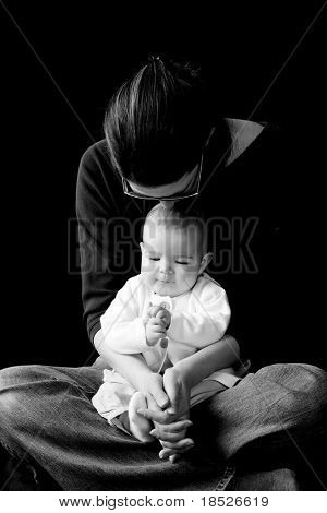 mother holding infant on lap, black and white image