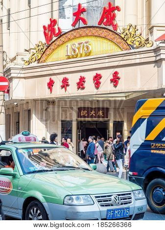 Shanghai, China - Nov 4, 2016: Along Nanjing Road Pedestrian Street - Shen Dacheng Restaurant (Chinese characters) occupies a historic building. Crowds of people and cab at front.
