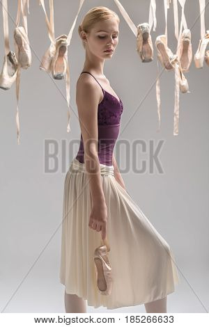 Pretty ballerina with closed eyes in a violet top and a cream skirt stands sideways on the gray background in the studio. Around her there are many hanging beige pointe shoes. She holds a ballet shoe.