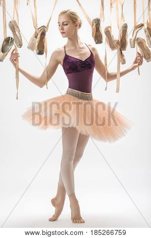 Cute ballerina in a violet top and a peach tutu stands on the toes on the light background in the studio. Around her there are many hanging beige pointe shoes. She holds ribbons of the ballet shoes.